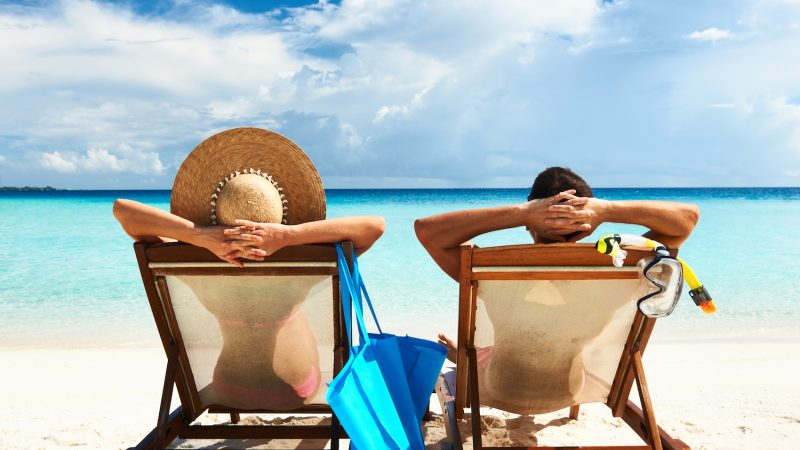 A picture of a couple sitting on the beach in chairs